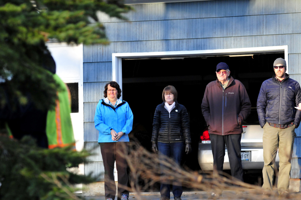 Joe Lemieux, second from right, watches as Waterville Public Works employees cut down a spruce tree Monday at his home in Fairfield. Lemieux donated the tree to the city of Waterville for Christmas. Also watching are nieces Patricia Hildreth, left, and Bernadette LaCroix and Parks and Recreation Director Matt Skehan.