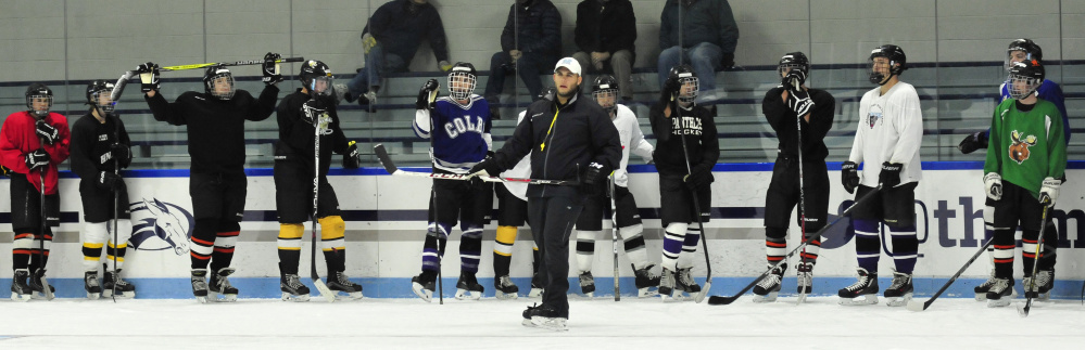 Kennebec RiverHawks coach Jon Hart, center, leads his team through practice on Monday at Colby College's Alfond Rink in Waterville.