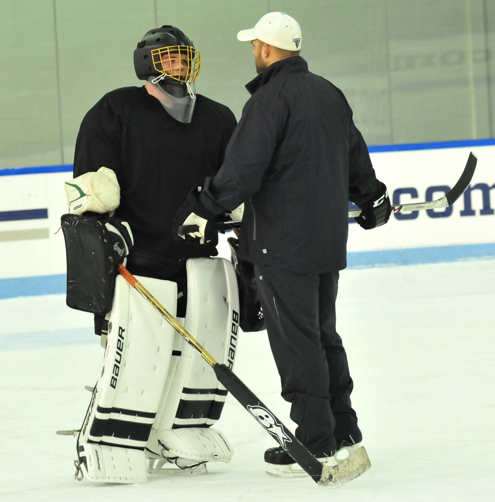 Kennebec RiverHawks coach Jon Hart talks to goalie Ben Grenier during practice Monday at Colby College.