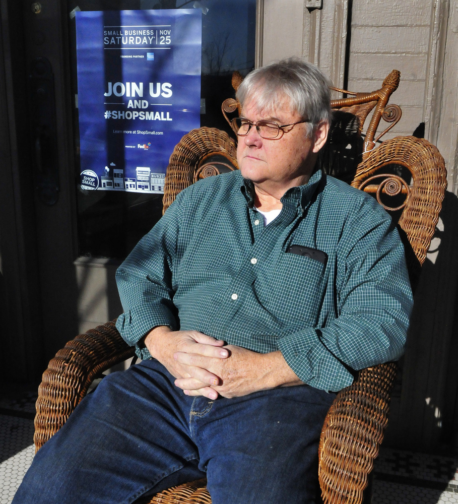 Downtown merchant Greg Salisbury relaxes on Tuesday in a chair outside his Hilltop Antiques store in Skowhegan after he put up a sign for this weekend's Small Business Saturday event.