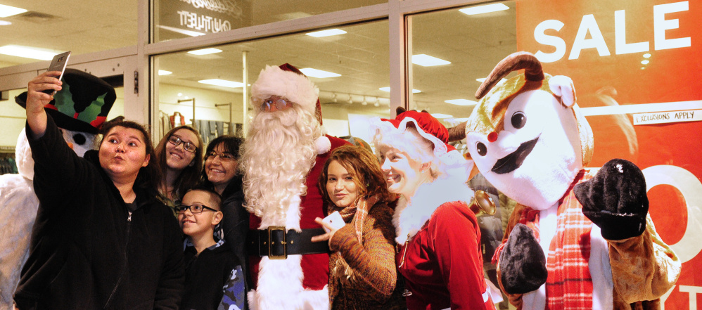 Black Friday shoppers take a selfie with Christmas characters Nov. 25, 2016, at the Marketplace at Augusta.