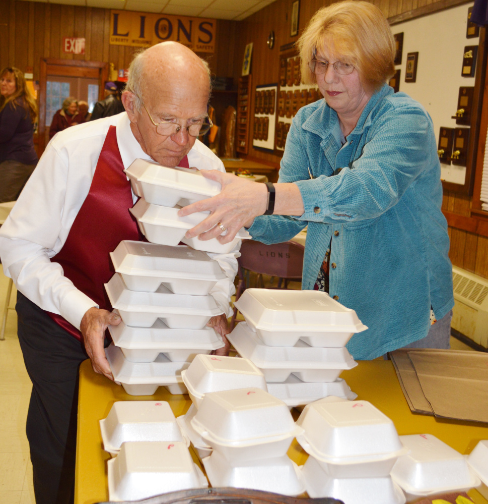 Tim Chase, left, and Carol Jones, help with the Thanksgiving meal preparation.