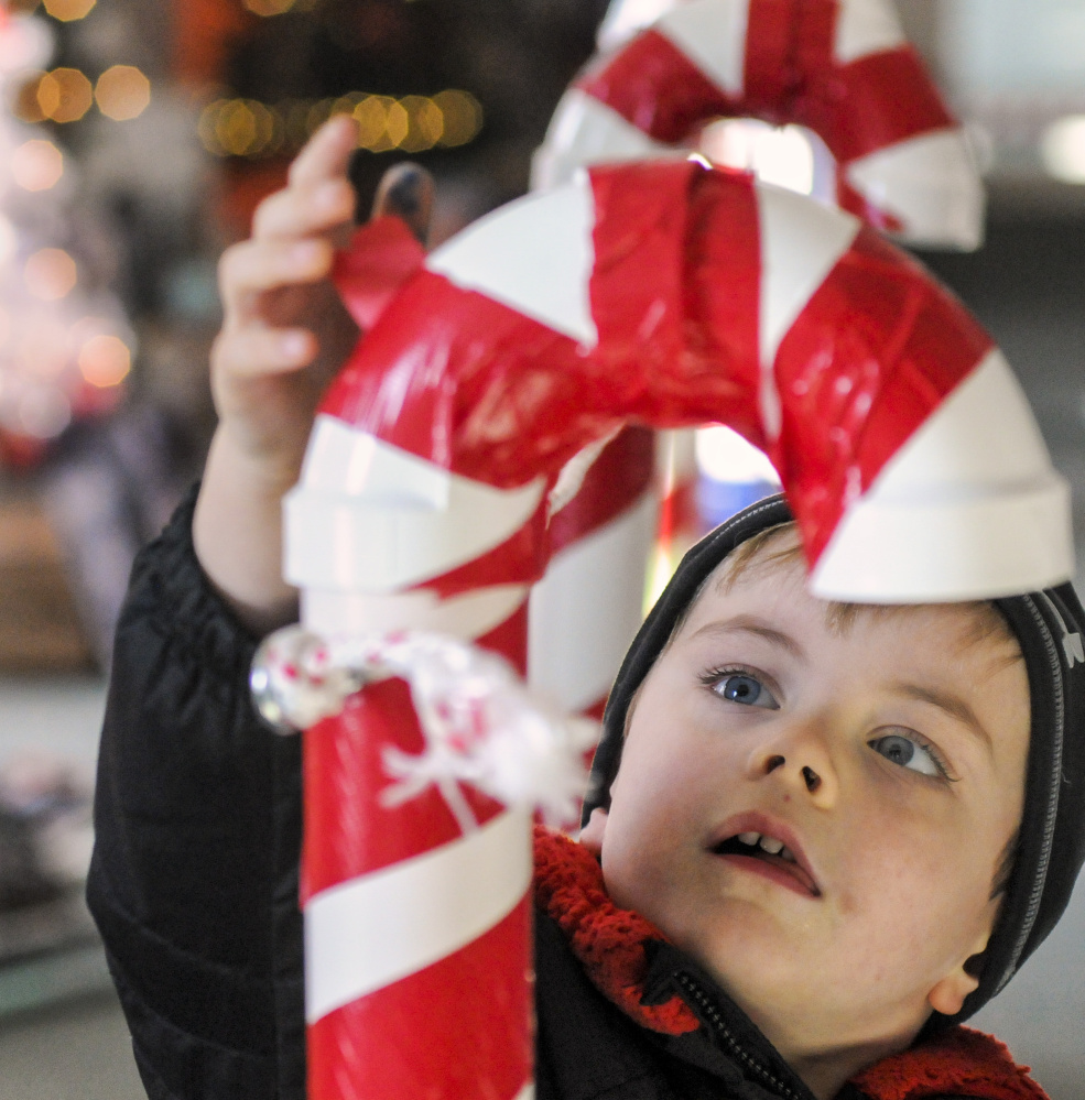 Nicky Mitchell, 4, of Gardiner, drops a ticket into a PVC pipe candy cane to vote for one of his favorite trees Friday at the River of Trees event in downtown Augusta.
