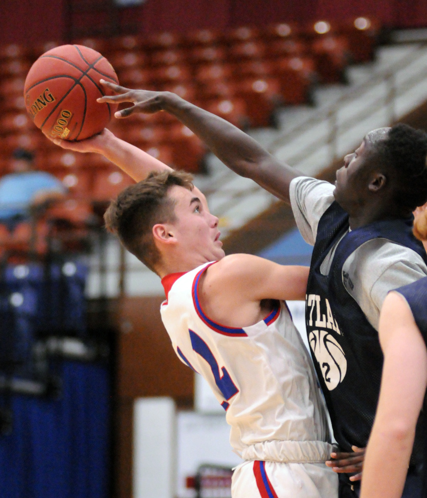 Messalonskee's Tucker Charles, left, tries shoot over Portland's Emmanuel Yugu on Friday at the Augusta Civic Center.