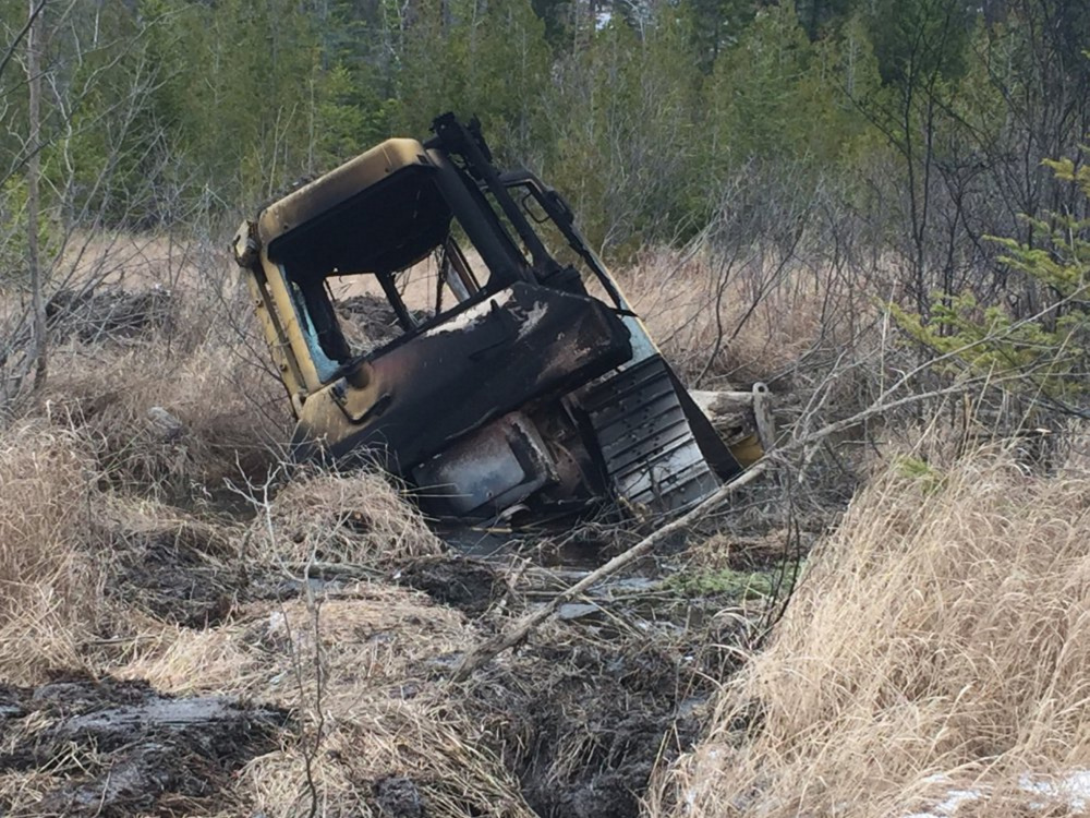 This bulldozer, owned by Cousineau Wood Products of Wilton, was found by hunters earlier this month off Beech Hill Road in Sandy River Plantation, where it had been set on fire.