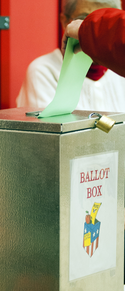 A voter drops a ballot into the ballot box Tuesday at the Winthrop Town Office, where polls are open until 8 p.m.