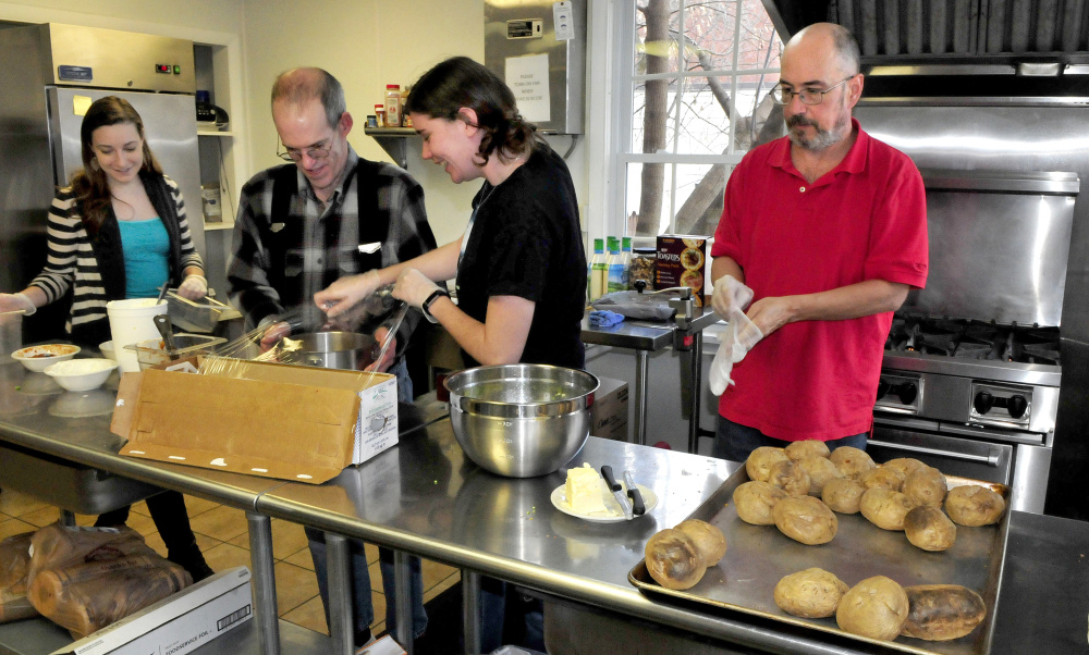 High Hopes Clubhouse unit coordinators Kristen Cormier, left, and Kaelee Tanner, center, work with members Richard Gilbert, second from left, and Scott Dubay after lunch Wednesday at the Waterville organization. The organization has been recognized for having 79 percent of its members employed.