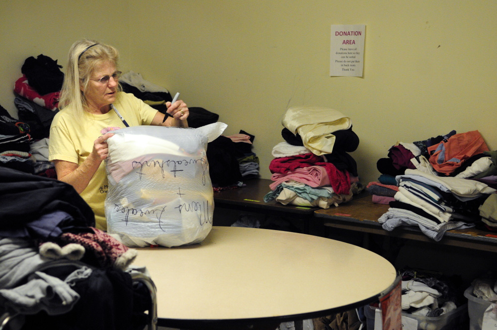 Volunteer Judy Colomy sorts clothes donated to Addie's Attic on Thursday at St. Mark's Parish Hall in Augusta. Bridging the Gap volunteers were rearranging the building's basement so that there will be more room for the Augusta Community Warming Center to use when it opens Friday.