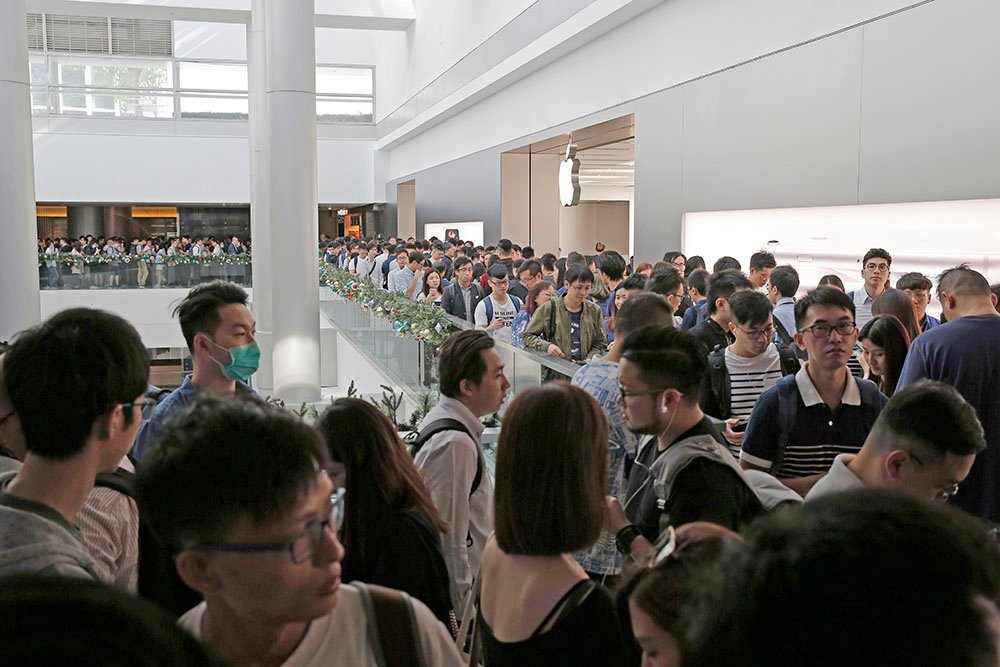 Customers line up to buy the new iPhones they previously reserved online at an Apple Store in Hong Kong, Friday.