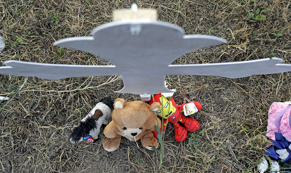 Stuffed animals rest at the base of a cross at a makeshift memorial for victims near the scene of a shooting at the First Baptist Church of Sutherland Springs, Tuesday.