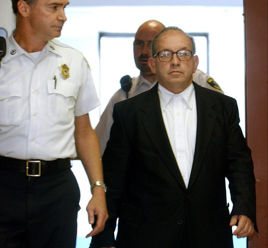James Talbot, a Jesuit priest at the time, is escorted into Suffolk Superior Court in Boston on Sept. 19, 2002, for arraignment on charges of rape, and indecent assault and battery.