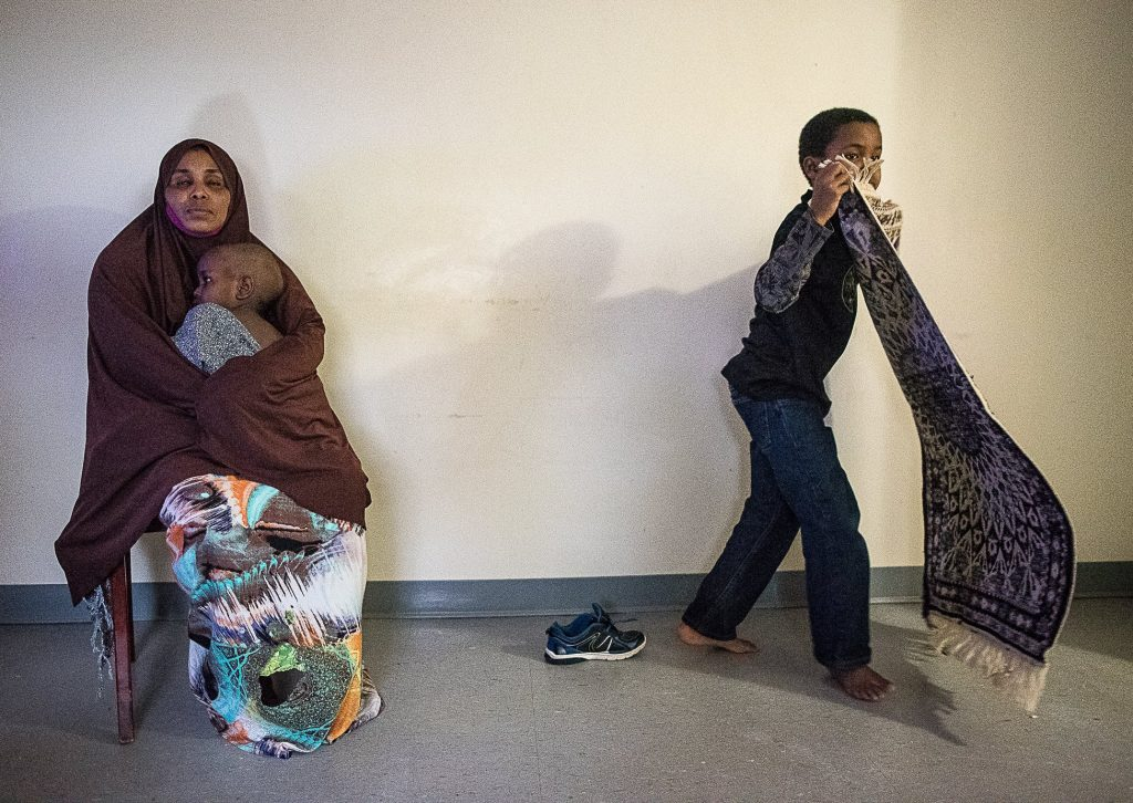 """Kadra Ahmed"" sits in her living room in Lewiston with her 2-year-old son, who was diagnosed with lead poisoning while living at their former apartment. Her 9-year-old son picks up his prayer rug. ""All our life is dependent on his sickness,"" Ahmed said through an interpreter. ""Our life is just changing."""