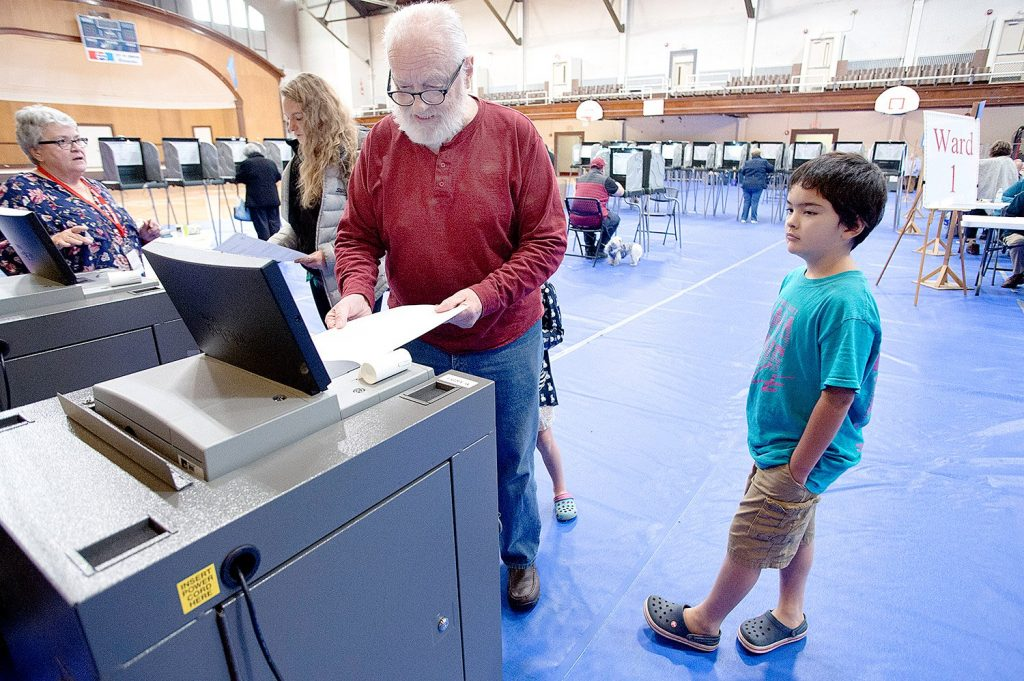 Jon Pitman casts his ballot at the Lewiston Memorial Armory on Tuesday. Pitman's grandchildren, Kazuchi and Ayana Suzuki, came with him.