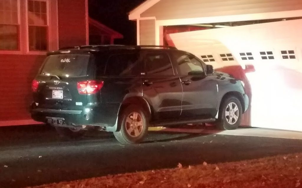 Police say Nelson Brown crashed into this SUV hard enough to push it into the garage and knock the garage off its foundation.