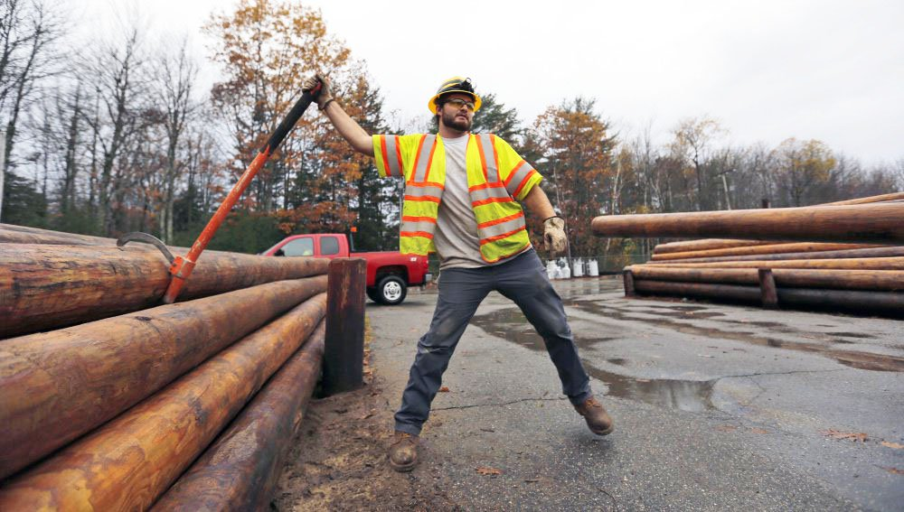 Central Maine Power Co. worker Jason Valera loosens a utility pole from a pile before it's lifted onto a trailer in Brunswick on Monday.