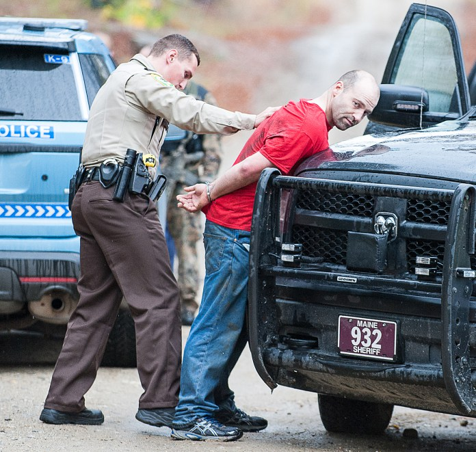 An Oxford County Sheriff's deputy pats down Jason Merriam on Bradeen Road in Sumner on Friday morning after he was brought out of the woods where Maine State Police Tactical Team members took him into custody.