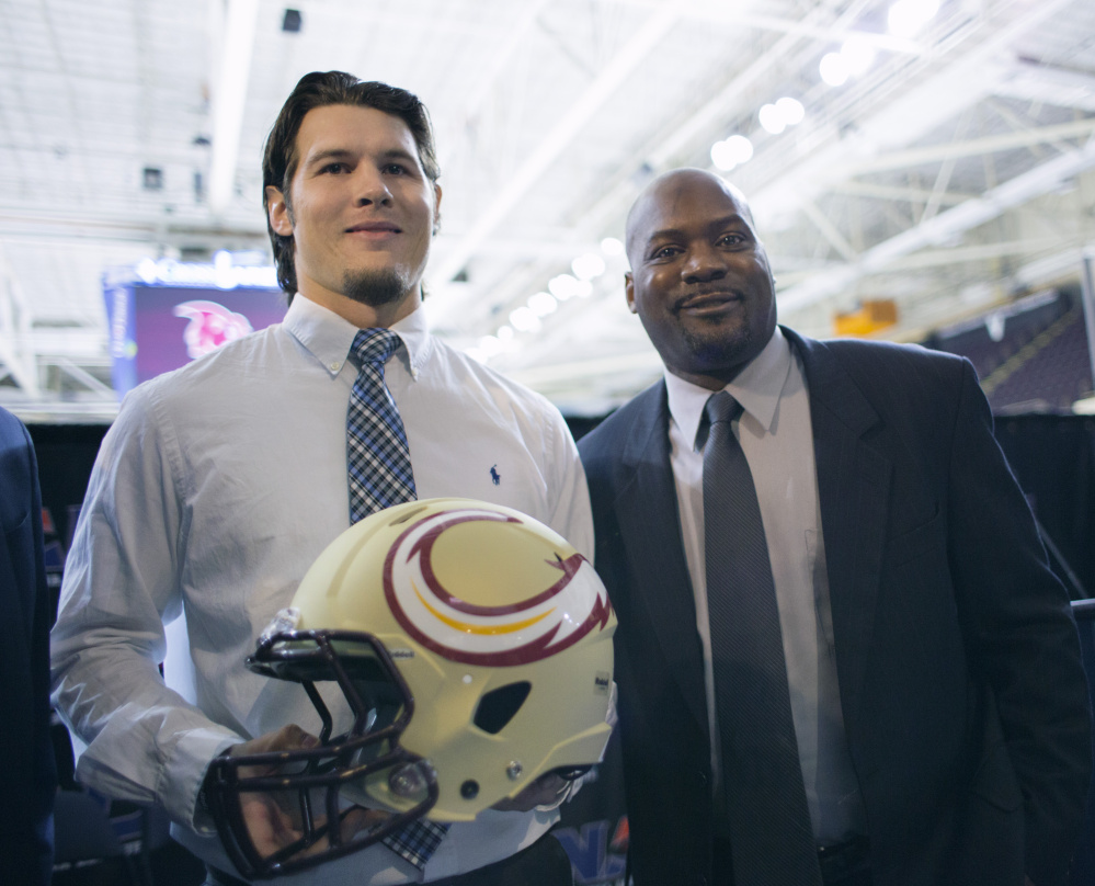 Jonathan Bane, quarterback of the Maine Mammoths, a new National Arena League football team based in Portland, displays the team's helmet design with head coach James Fuller after a news conference Tuesday at Cross Insurance Arena. (Photo by Derek Davis/Staff photographer)