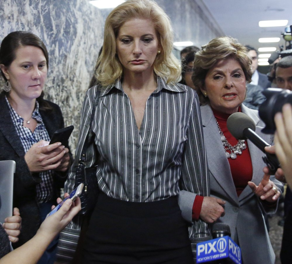 Gloria Allred, right, and her client Summer Zervos, center, push through the media as they leave Manhattan Supreme Court on Tuesday after a hearing in Zervos's defamation lawsuit against President Trump.
