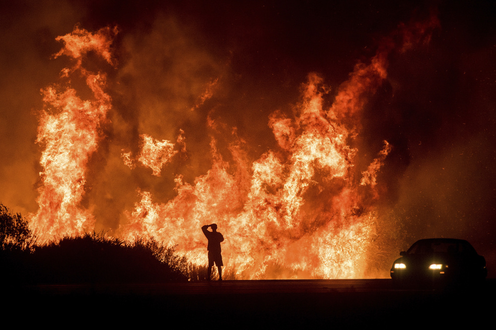 A motorist on Highway 101 watches flames from the Thomas fire leap above the roadway north of Ventura, Calif., on Wednesday.  As many as five fires have closed highways, schools and museums, shut down production of TV series and cast a hazardous haze over the region.