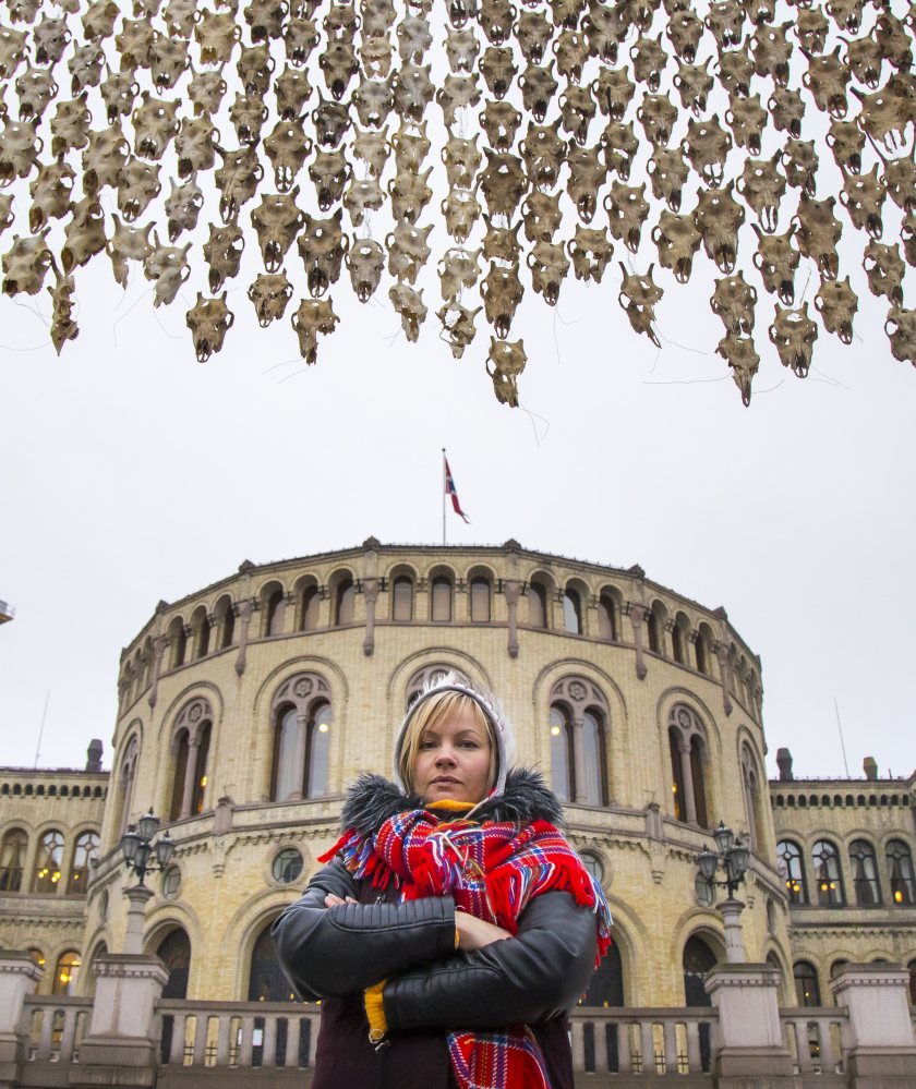 To protest culling reindeer herds, Maret Anne Sara poses by her artwork of 400 bullet-ridden reindeer skulls near Parliament in Oslo, Norway, Wednesday.