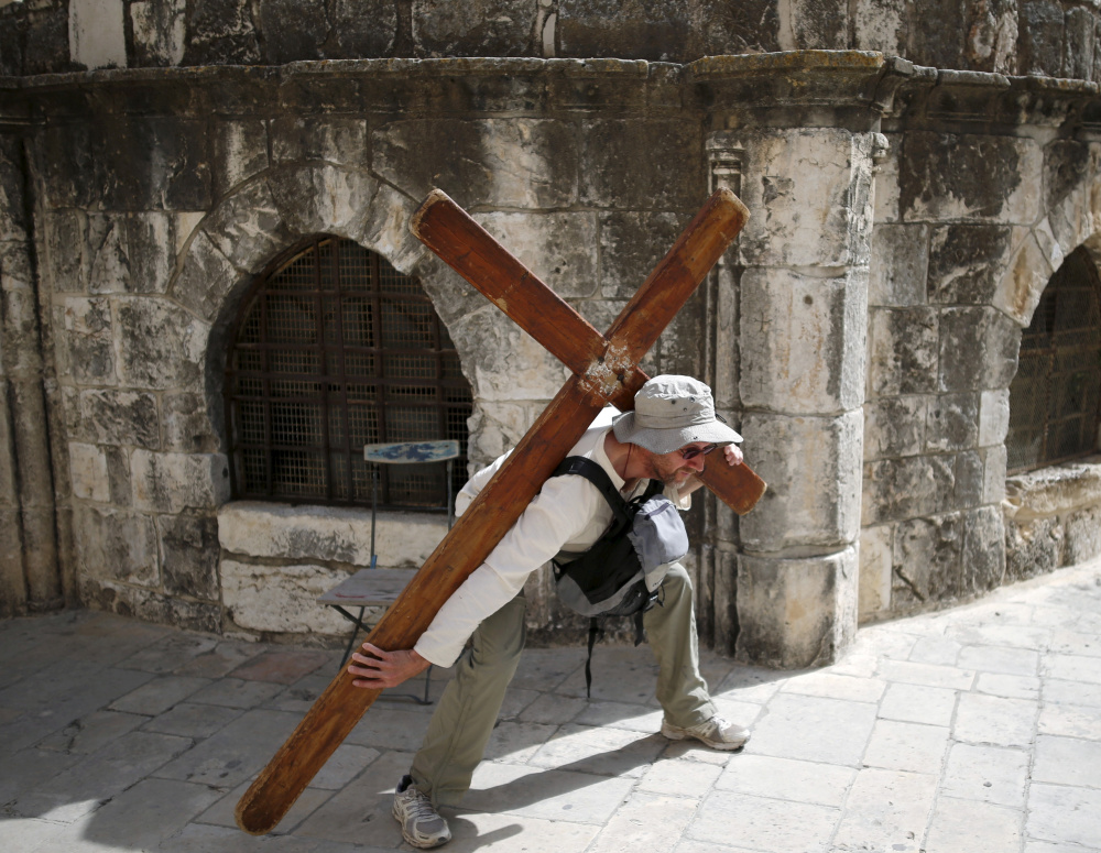A Christian worshipper, left, poses last year for a picture on Good Friday near the Church of the Holy Sepulchre in Jerusalem. Above, a Jewish worshipper prays at the Western Wall, Judaism's most holy site for prayer.