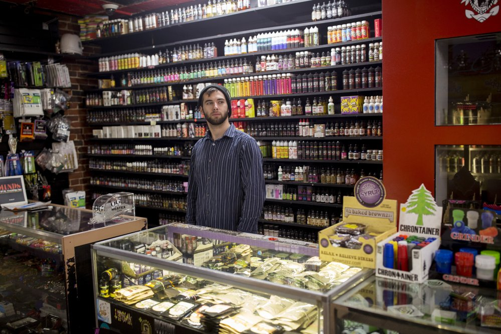 "Ryan Purington, an employee at Lucky Juju in Portland, works behind the counter at the shop Thursday. The store started stocking vaporizers last month and Purington said they are ""flying off"" the shelves because they are discreet, easy to use and powerful."