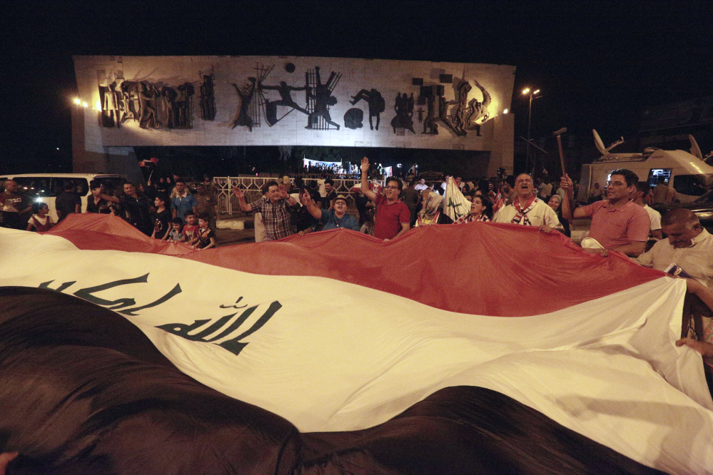 Iraqis celebrate while holding a giant national flag after Iraqi Prime Minister Haider al-Abadi declared victory against the Islamic State group in Mosul, Iraq, in July. Iraq said Saturday that its war against ISIS is over after more than three years of combat operations drove the extremists from all of the territory they once held.