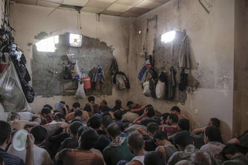 Suspected Islamic State members sit inside a small room in a prison south of Mosul, Iraq, in July. Prime Minister Haider al-Abadi announced Saturday that Iraqi forces were in full control of the country.