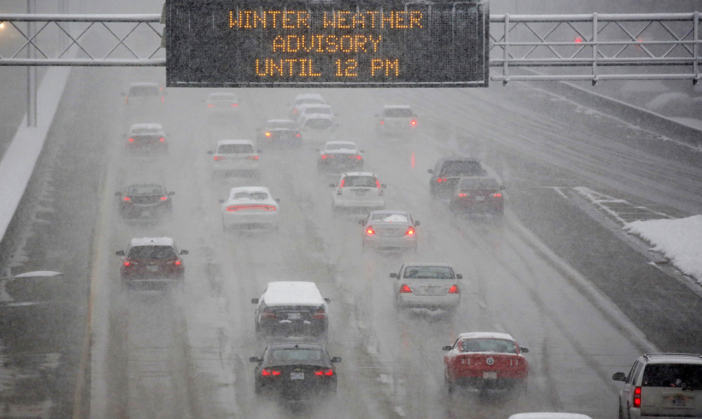 A heavy morning snow falls in Jackson, Miss., Friday, as an electronic sign posts a winter weather advisory on Interstate 55.