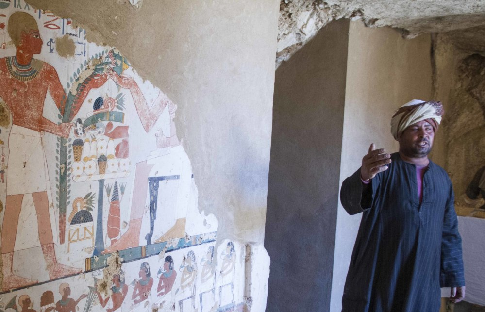An Egyptian guard stands next to a funeral mural inside a newly discovered tomb on Luxor's West Bank. One of the two tombs has five entrances that leads to a hall and contains funerary masks, clay vessels and a mummy.