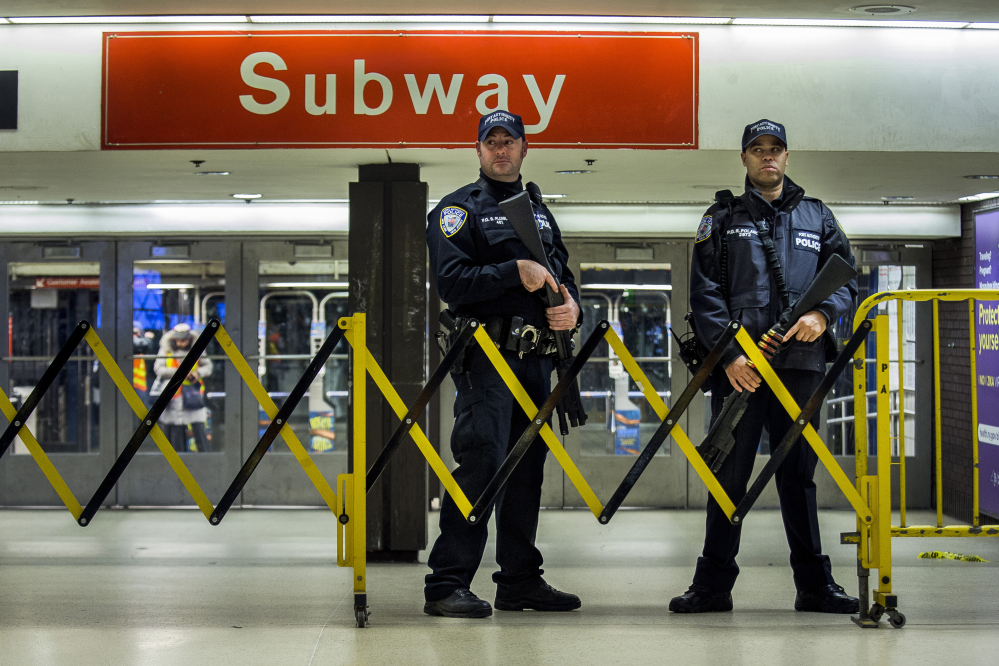 Police stand guard inside the Port Authority Bus Terminal following an explosion near Times Square on Monday in New York. Police said a man with a pipe bomb strapped to his body set off the crude device in a passageway under 42nd Street between Seventh and Eighth avenues.