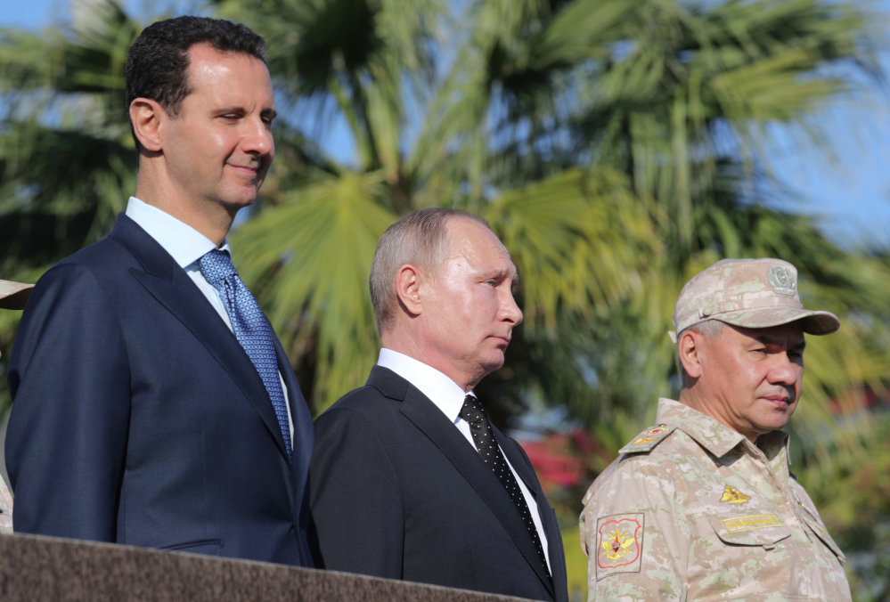 From left, Syrian President Bashar Assad, Russian President Vladimir Putin and Russian Defence Minister Sergei Shoigu watch troops march at Syria's Hemeimeem air base Monday.