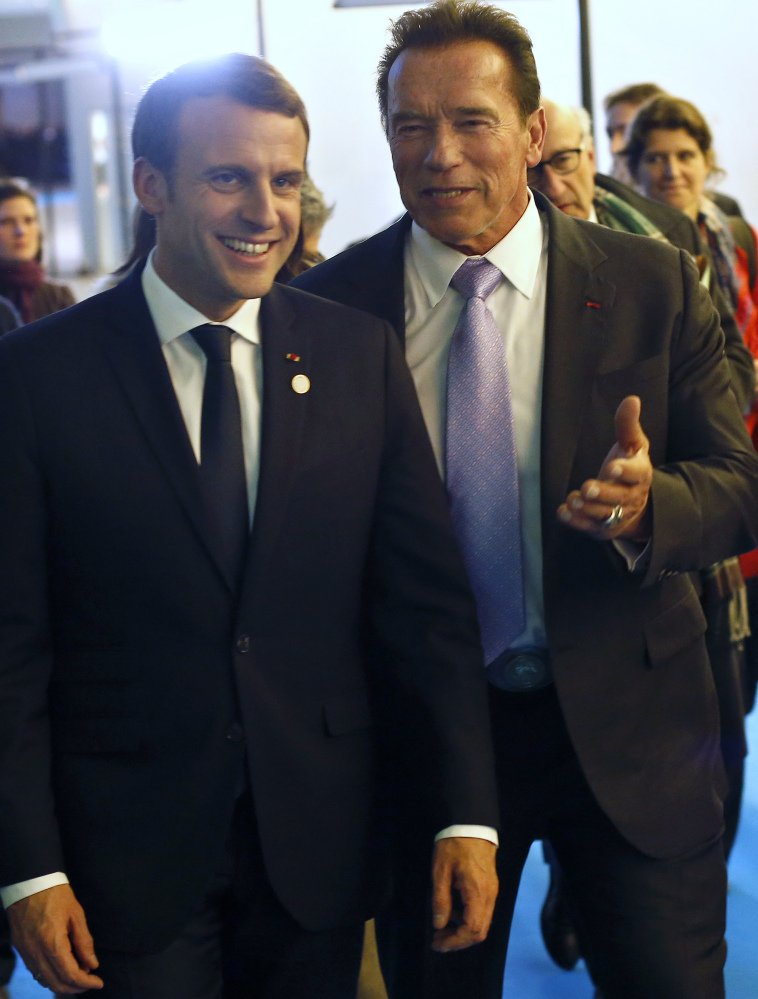 France's President Emmanuel Macron, left, and Arnold Schwarzenegger leave the One Planet Summit near Paris, Tuesday. American leaders there said the world will go greener with or without President Trump.accord.