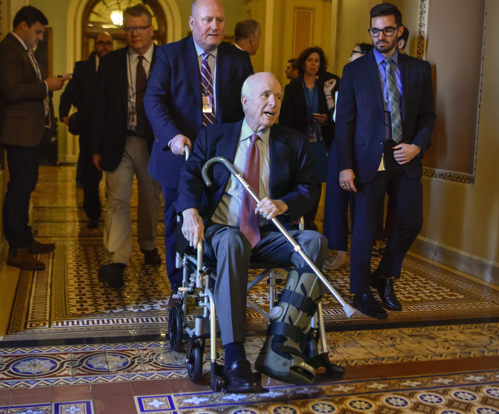 Sen. John McCain, R-Ariz., makes his way to a meeting Dec. 1 in Washington about the Republican tax bill. An Achilles tendon tear in early November put him in a walking boot.