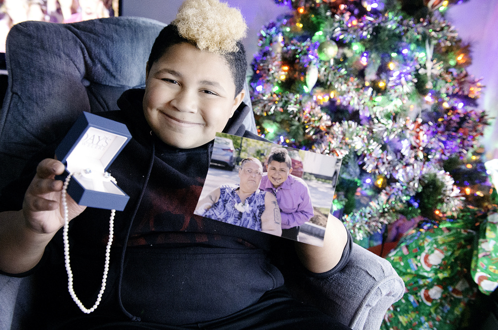 "Kaden James, 11, of Turner holds the pearl necklace and earrings that will be a very unexpected Christmas gift for his mother, Michelle James, seen in the photo. ""He was so polite ... and so appreciative,"" says Day's Jewelers Assistant Manager Vanessa Phipps. ""It was really kind of what Christmas is all about."""
