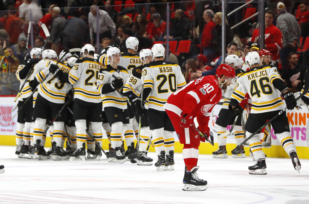 Bruins players celebrate their 3-2 win after Brad Marchand's goal just 35 seconds into overtime Wednesday night in Detroit.