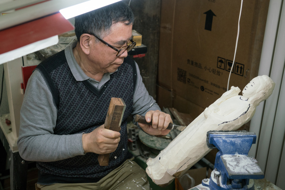 Carving artist Li Chunke works on an ivory Gautama Buddha statue in his Beijing workshop. He's worried his profession will start to die out because of China's ban on ivory sales.