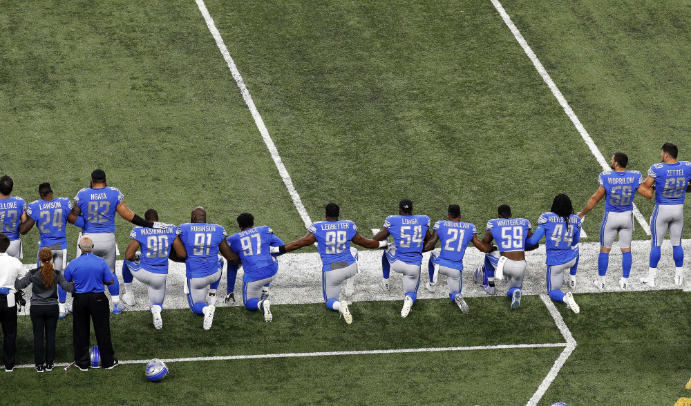 Detroit Lions players take a knee during the national anthem before an NFL game against the Atlanta Falcons in Detroit on Sept. 24, 2017.