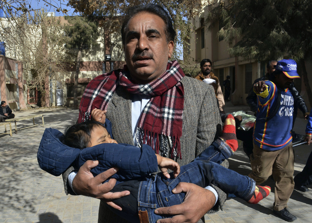 A volunteer rescues a child while others remove a body following the suicide attack on a church in Quetta, Pakistan, on Sunday. One assailant was killed and the other wounded.