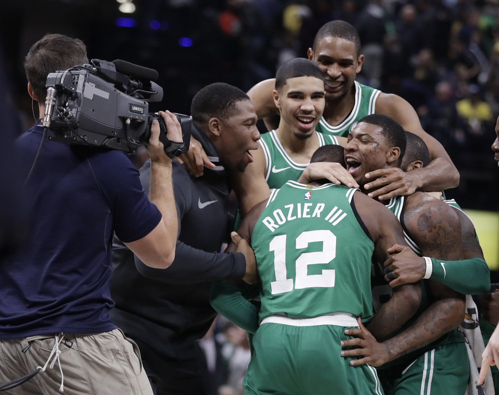 The Celtics' Terry Rozier (12) is mobbed by teammates after his steal and dunk in the finals seconds gave Boston a win over the Indiana Pacers on Monday night in Indianapolis.