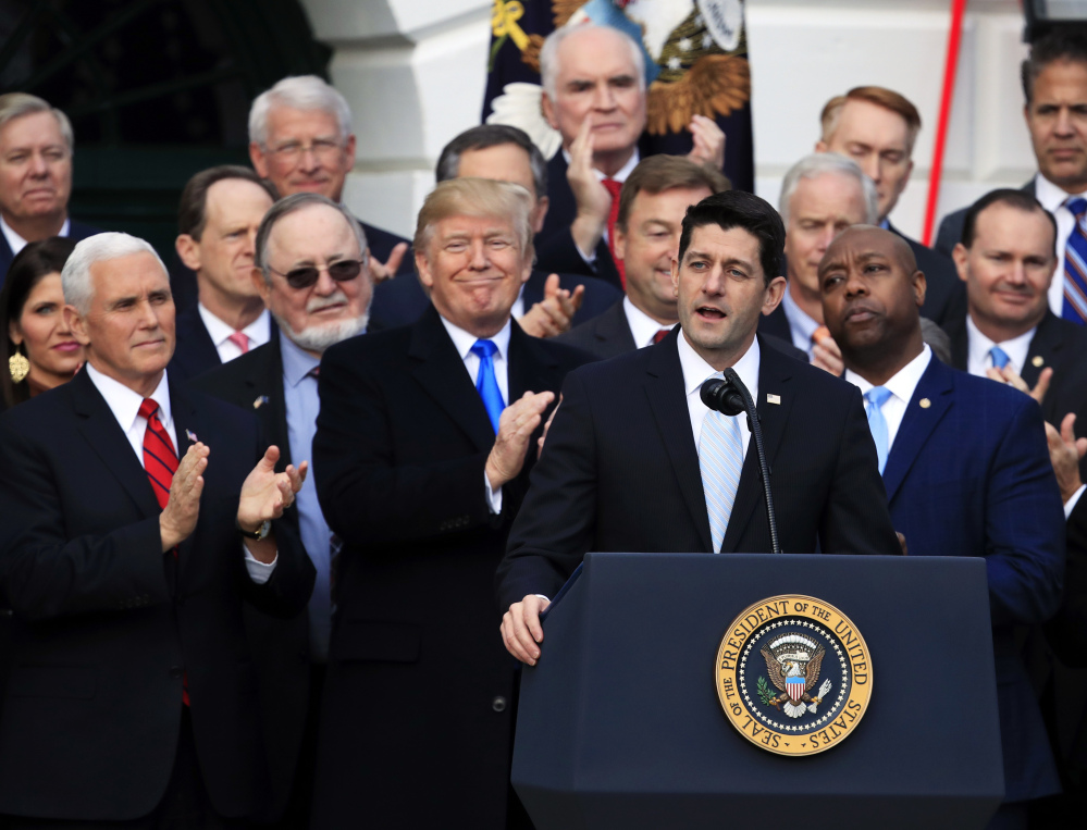 House Speaker Paul Ryan speaks while President Trump and Vice President Mike Pence applaud outside the White House on Wednesday as they celebrate the tax cut plan.