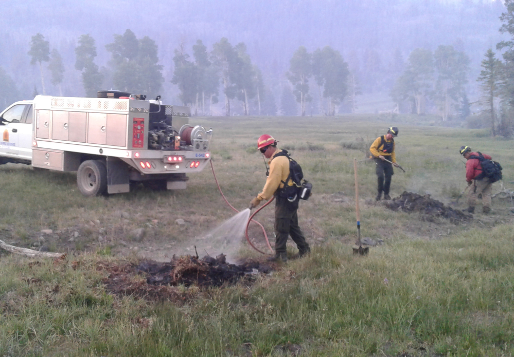 This photo from last July provided by Chubb shows Wildfire Defense Systems, Inc. firefighters mopping up spot fires on a client's property during a wildfire in Panguitch, Utah.