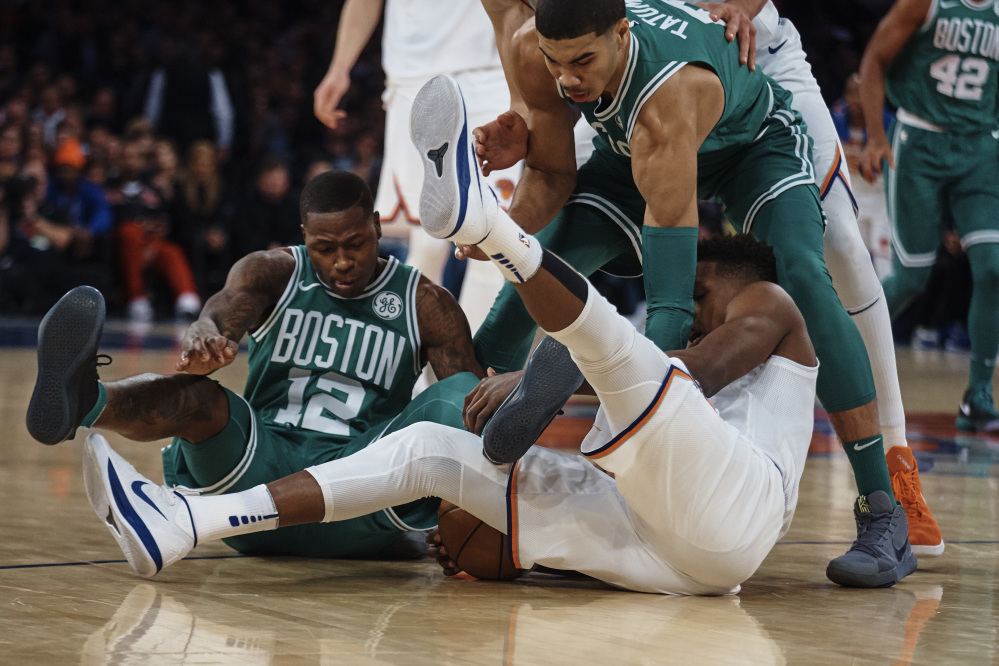 New York's Frank Ntilikina, bottom center, competes for the ball with Boston's Terry Rozier, left, and Jayson Tatum in the first half Thursday night in New York.