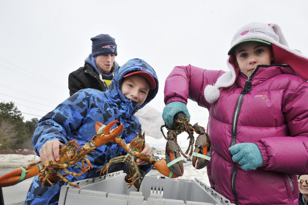 Lobsterman Noah Ames, his daughter Nadia, 10, right, and Aiden Willis, 9, give away lobsters to anyone in need Sunday in Thomaston. This year, Ames distributed over 400 pounds of lobster.