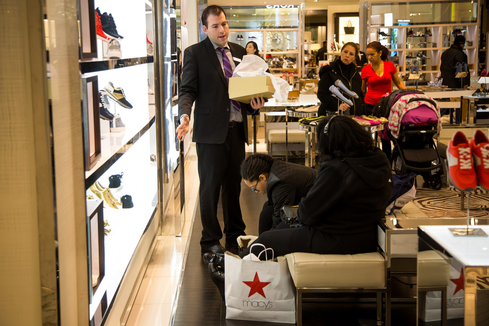 A Macy's employee, at left, helps customers at a department store in New York in 2016. Bloomberg/Michael Nagle