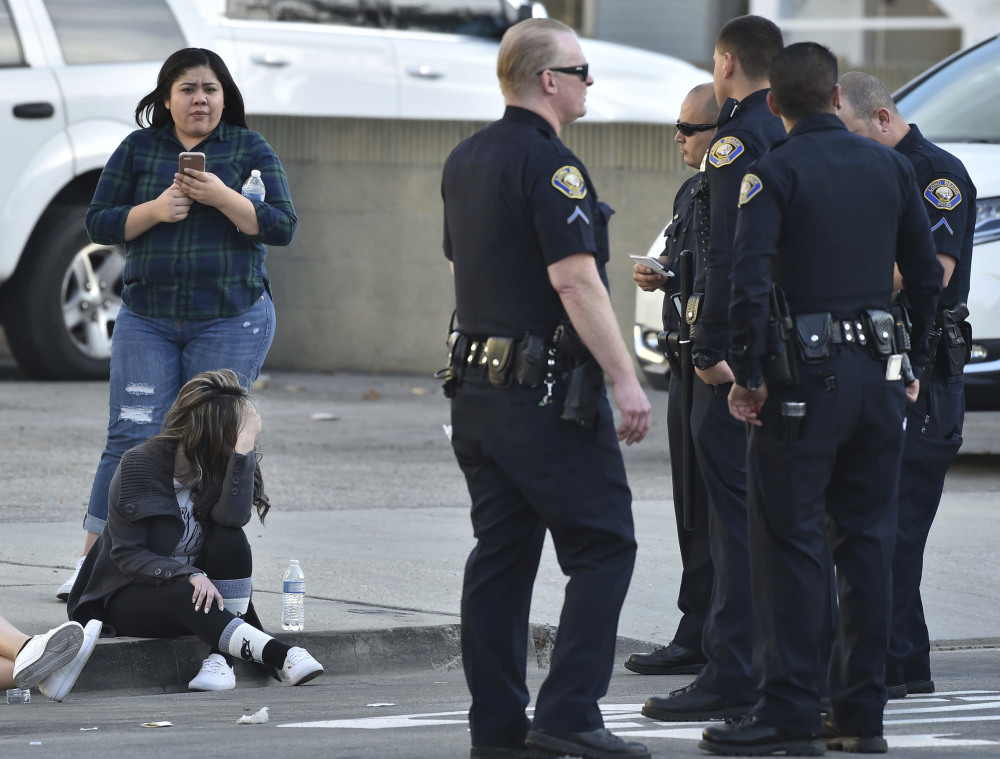 Workers from a nearby business wait by Long Beach, Calif., police Friday after a shooting that left one lawyer dead, another wounded and the shooter dead from a self-inflicted wound.