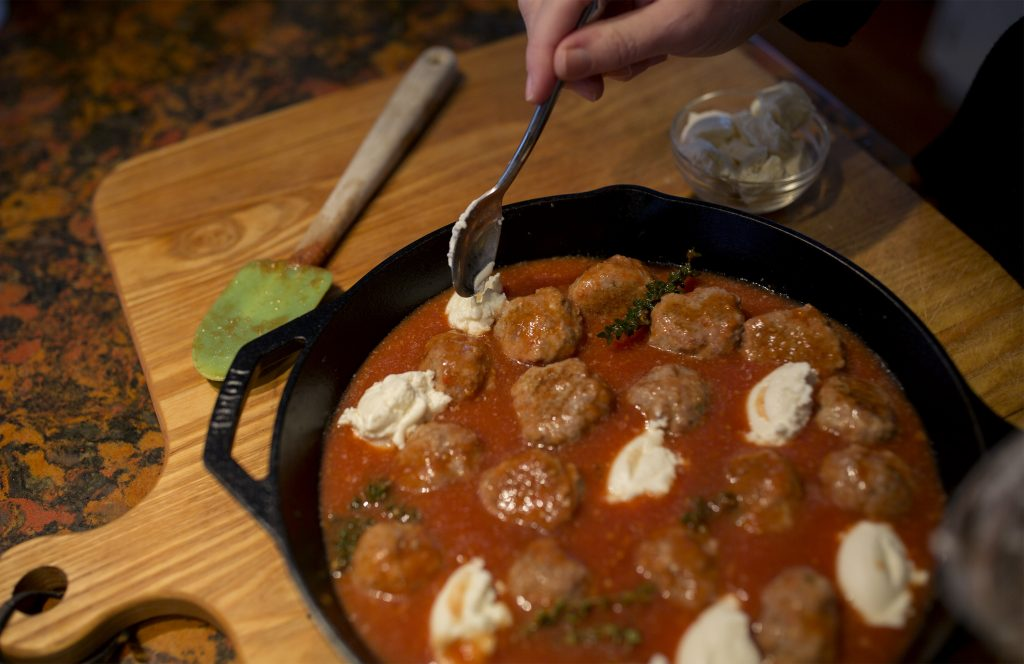 Christine Burns Rudalevige adds dollops of ricotta cheese to the veal meatball dish.