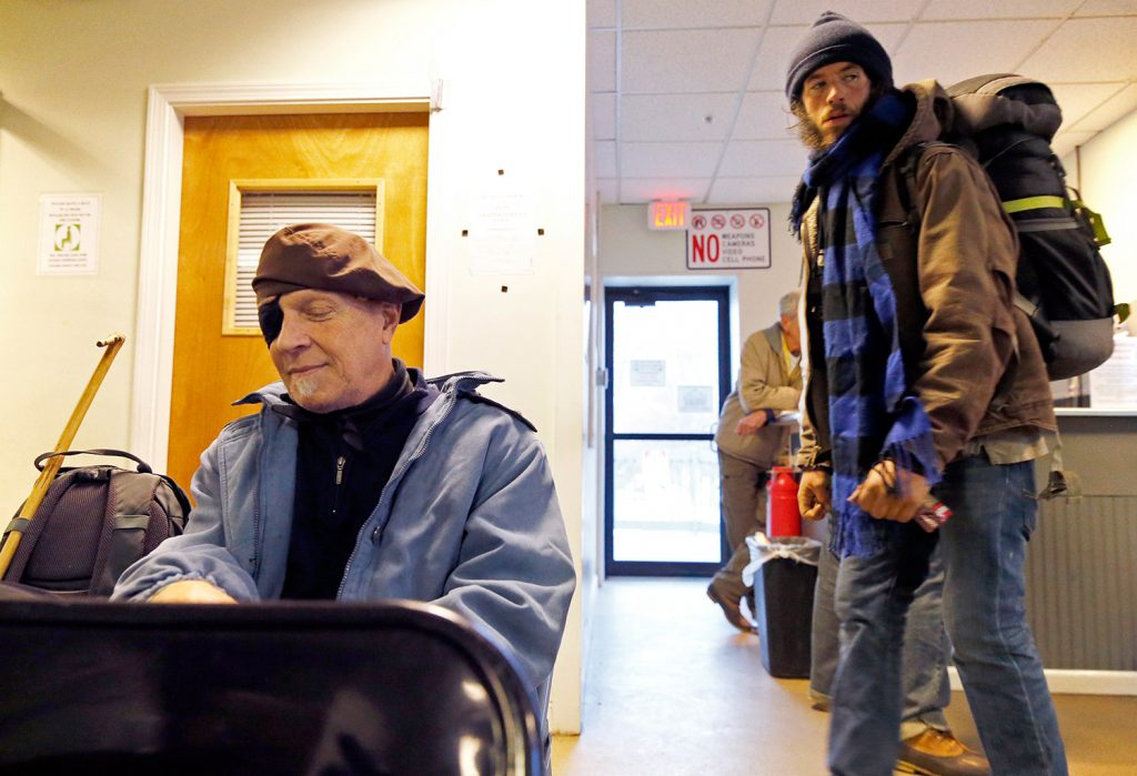 "Mark Elsner, left, sits in the day room Monday at the Oxford Street Shelter, which now offers round-the-clock services to the homeless. Before Monday, people who stayed overnight in the shelter had to leave in the morning, with no place to go. ""Outside is really hard,"" said Elsner, who has lived at the shelter for almost two months. ""This will be very helpful."""