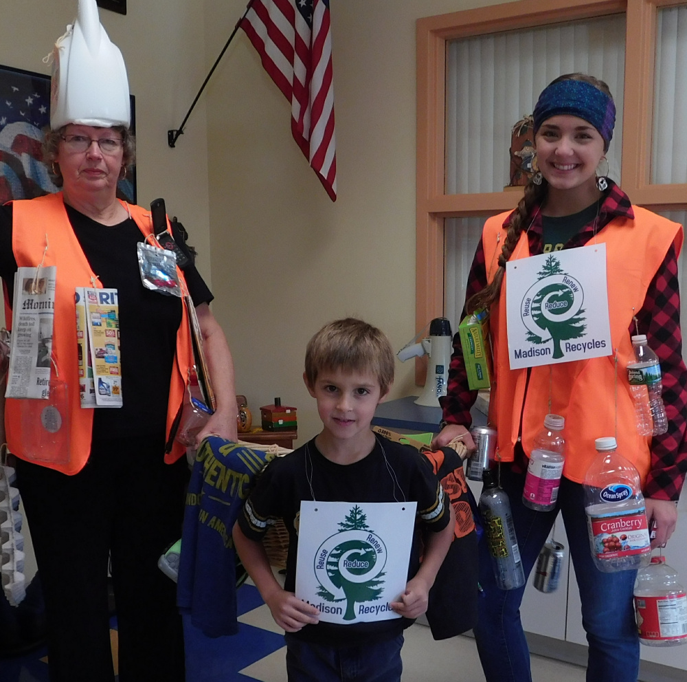 Madison Recycle Advisory Committee member Betty Vining, of Madison, left, Madison Elementary School kindergartner Levi Dube, of Starks, center, and Madison Area Memorial High School junior Jennifer Dean, a student representative of the Madison Recycle Advisory Committee.