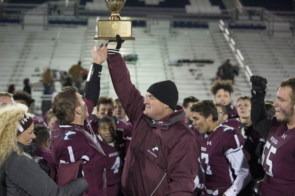 Maine Central Institute coach Tom Bertrand, right, holds aloft the Class C Gold Ball after the Huskies sank Cape Elizabeth in the state title game this season.
